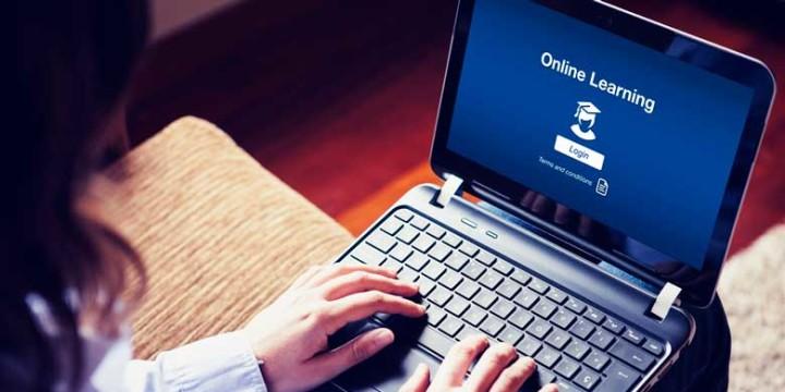 """""""Online Learning"""" na tela. Mulher com as mãos sobre o teclado do notebook"""